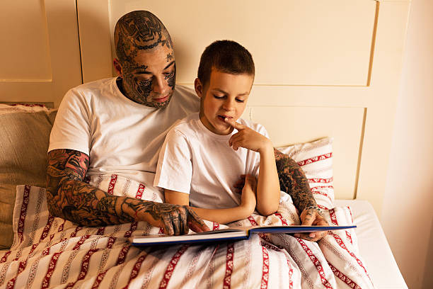 Young father reading a book to his son in bedroom. stock photo