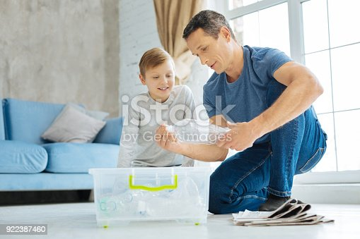 istock Young father showing his son how to crush plastic bottle 922387460