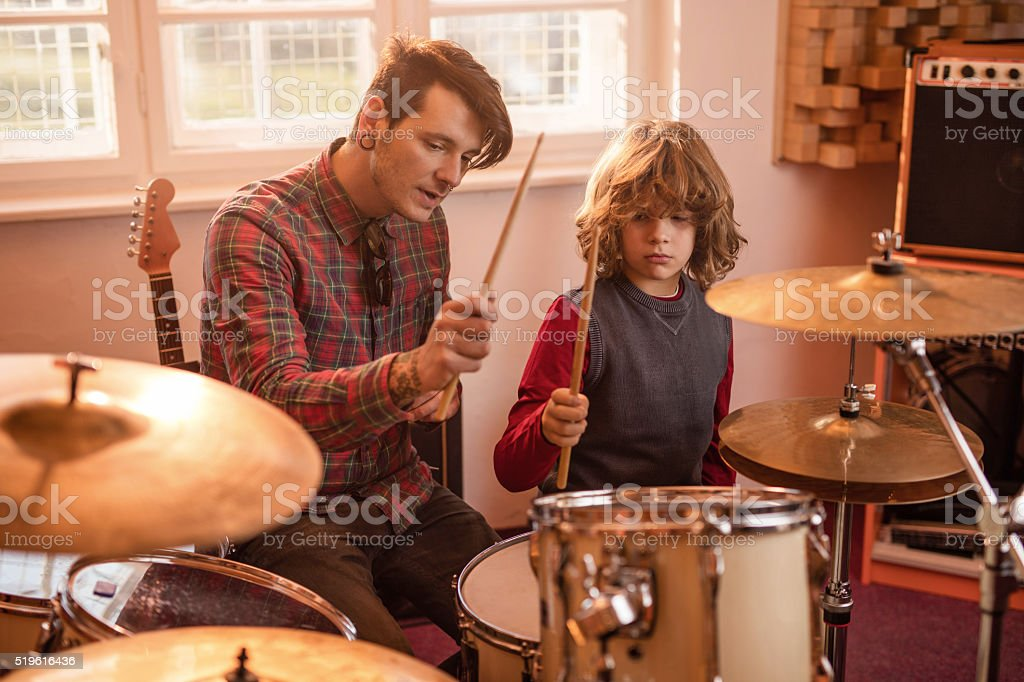 Young father showing his son how to play drums. stock photo