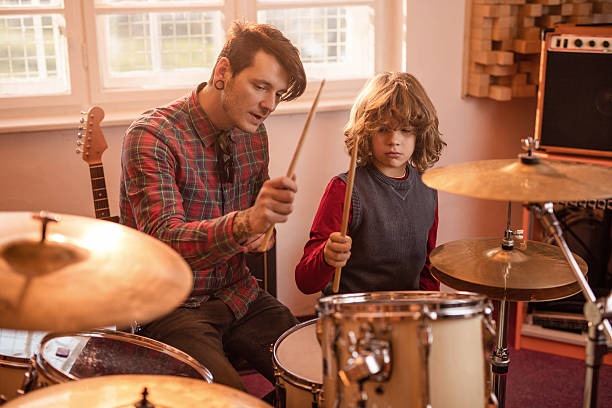 Young father showing his son how to play drums. Father teaching his little boy how to play drums in music studio. drum kit stock pictures, royalty-free photos & images