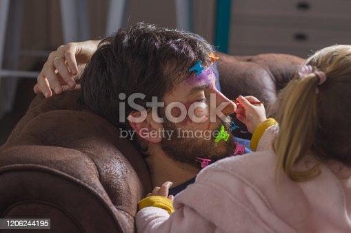 Father's Day celebration. Portrait of young father sleeping on the sofa while his little daughter paints her face with colorful watercolors and puts hair clips on her beard