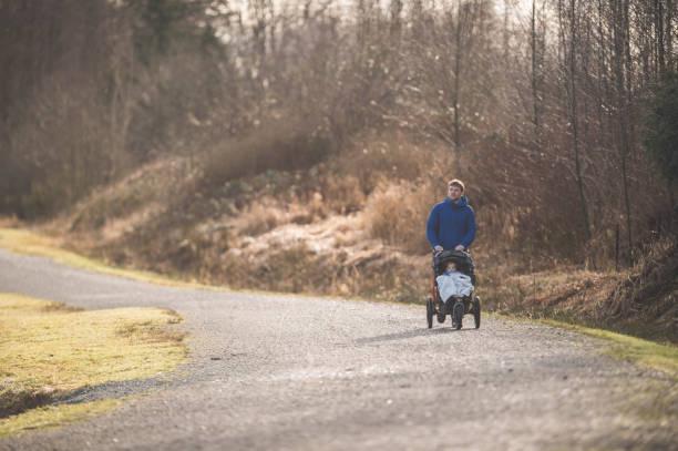 joven padre lleva a su hijo de niño para una caminata en la silla de paseo - padre que se queda en casa fotografías e imágenes de stock