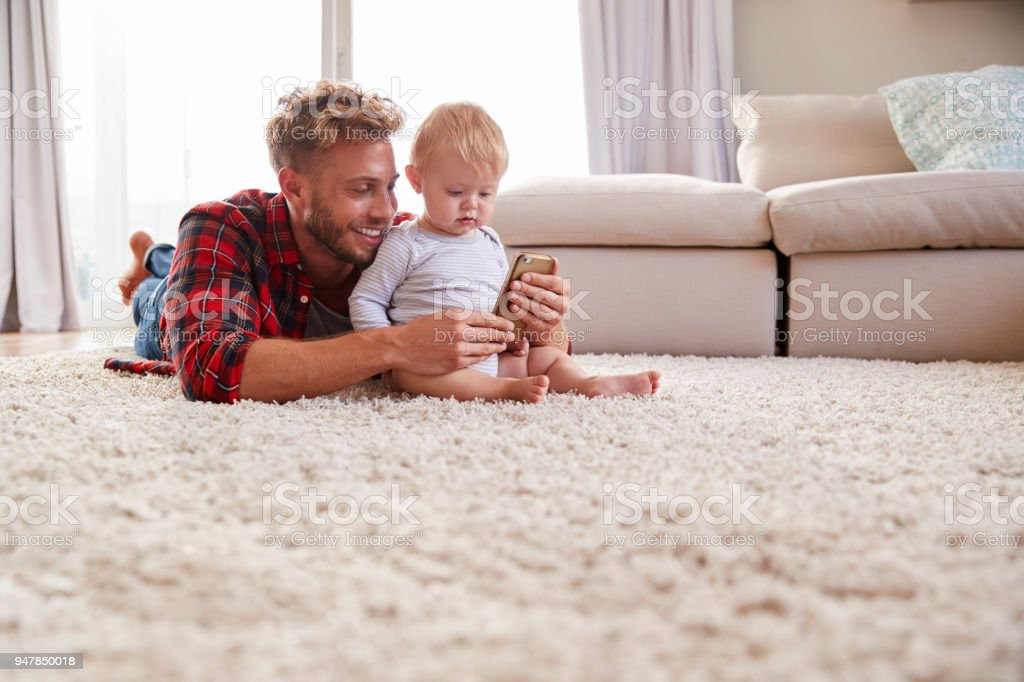Young father taking selfie with toddler son in sitting room stock photo