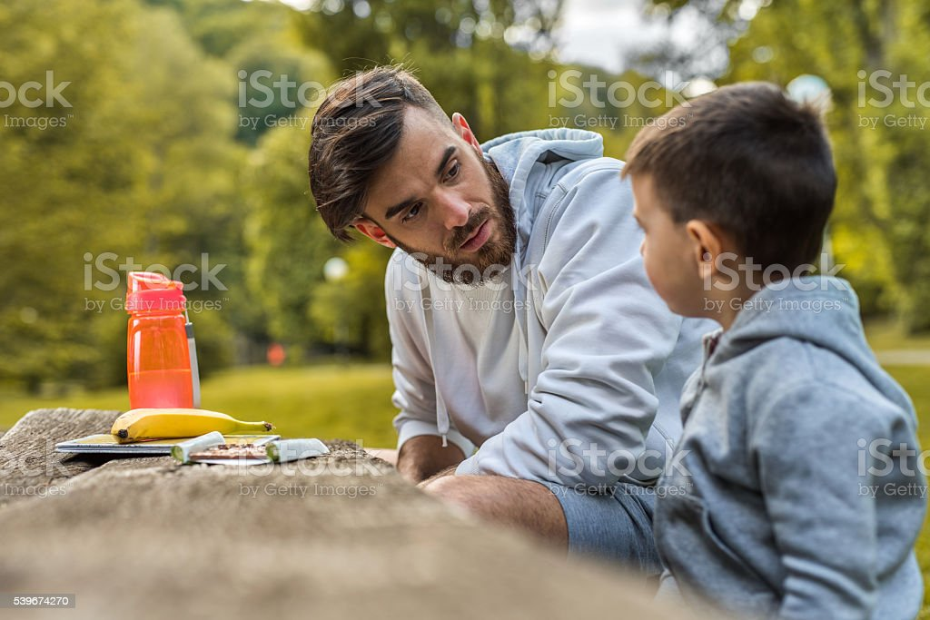 Young father talking to his small son in the park. stock photo