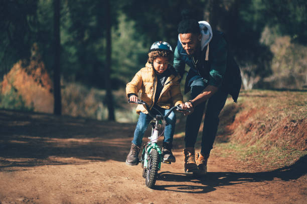 Young father teaching son how to ride bicycle in park stock photo
