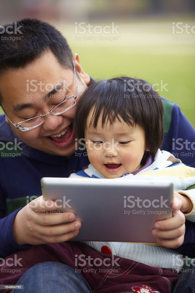 young father using tablet with her daughter outdoor royalty-free stock photo