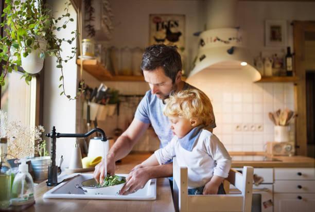 junger vater mit einem kleinkind jungen kochen. - wasch oder spülbecken stock-fotos und bilder