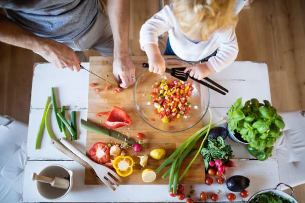 giovane padre con un bambino che cucina. - cucinare foto e immagini stock