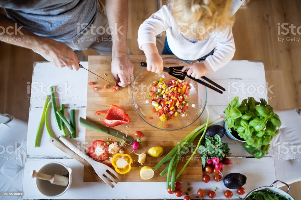 Young father with a toddler boy cooking. stock photo