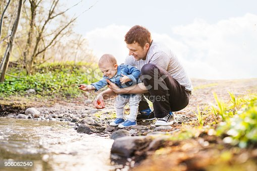 Happy young father with a toddler son playing outside. A small boy throwing rocks in water.