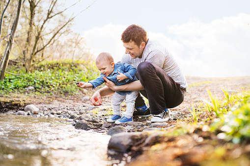 Young father with a toddler son playing outside.