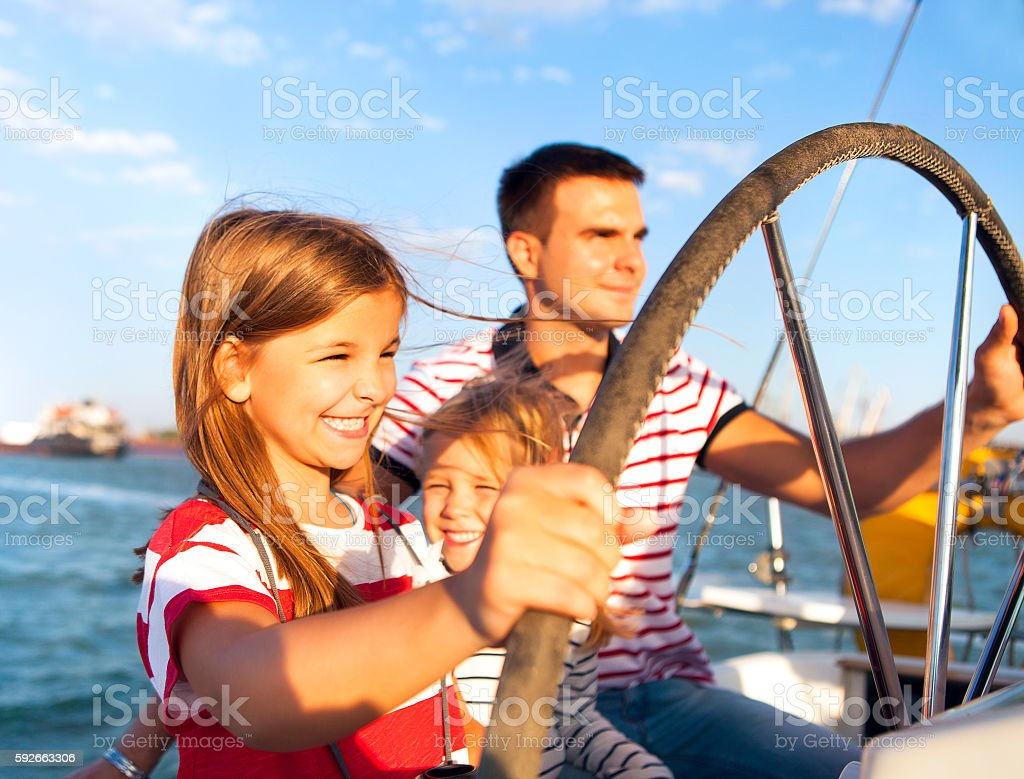 Young father with adorable daughters on a big boat stock photo