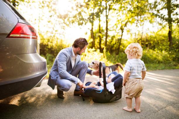 junger vater mit baby und kleinkind mit dem auto. - hunde träger stock-fotos und bilder