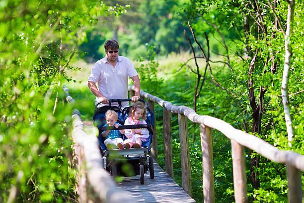 giovane padre con doppi passeggino nel parco - gemelle foto e immagini stock