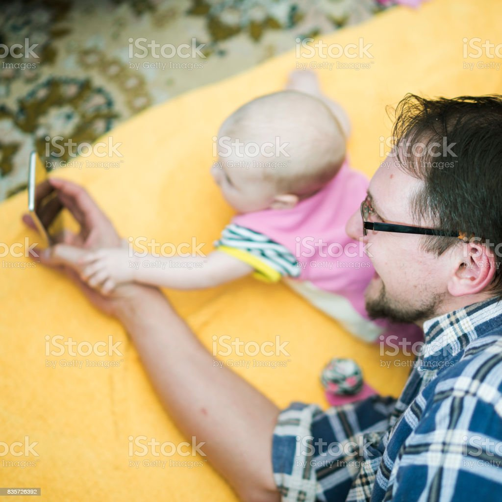 Young father with his baby daughter lying together on the floor and...