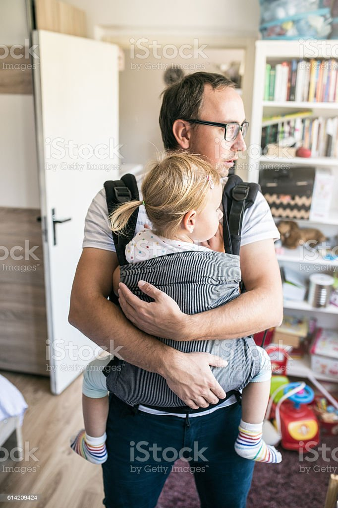 Young father with his daughter in baby carrier stock photo