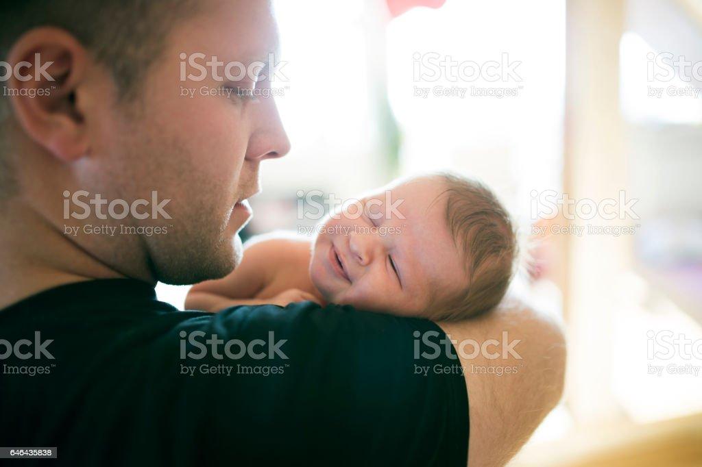 Junger Vater mit seiner neugeborenen Tochter im Arm – Foto