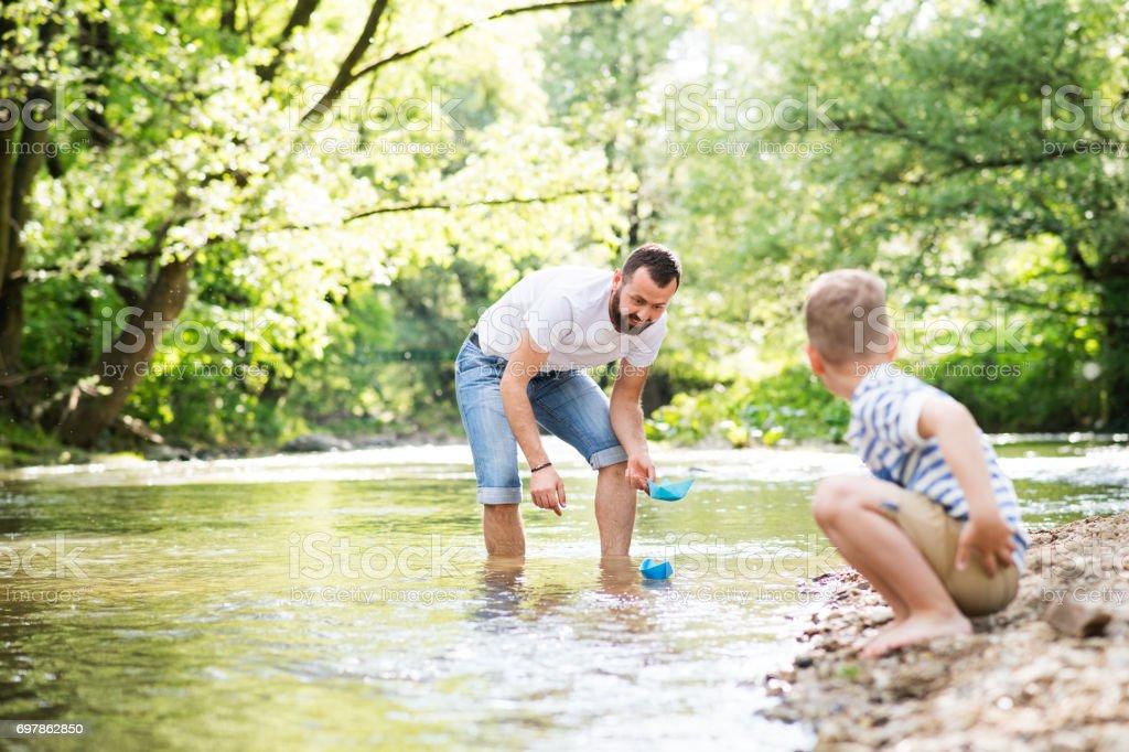 Jovem pai com o filho no rio, dia ensolarado de primavera. - foto de acervo