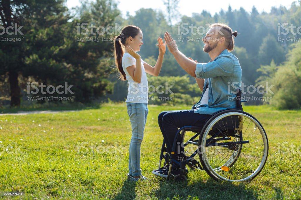 Joven padre con hija de movilidad deterioro celebrándolo - foto de stock
