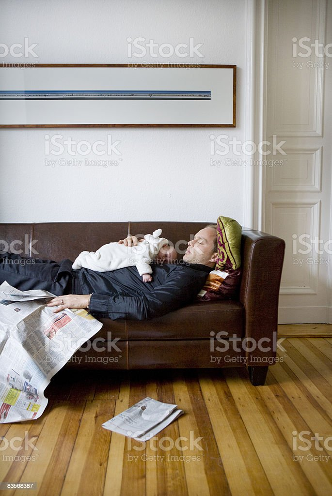 young father with newborn relaxing on sofa royalty free stockfoto