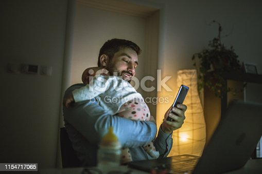 Young father working at home with his baby  girl