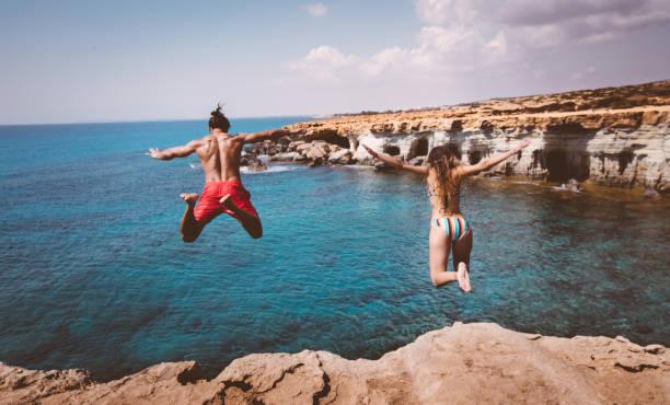 Genç korkusuz dalgıçlar çift okyanus içine uçurumdan atlamak stok fotoğrafı