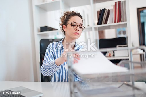 istock Young female administrative assistant at work. 1127110445