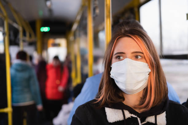 Young female adult commutes in a protective face mask. stock photo