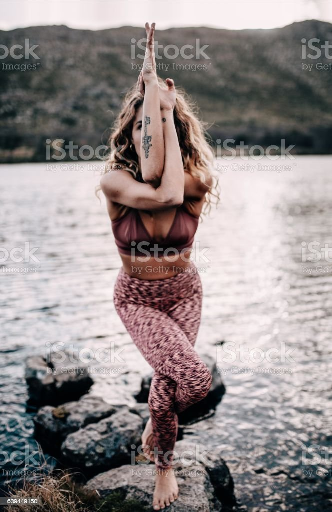 Young female adult doing yoga pose outdoors stock photo
