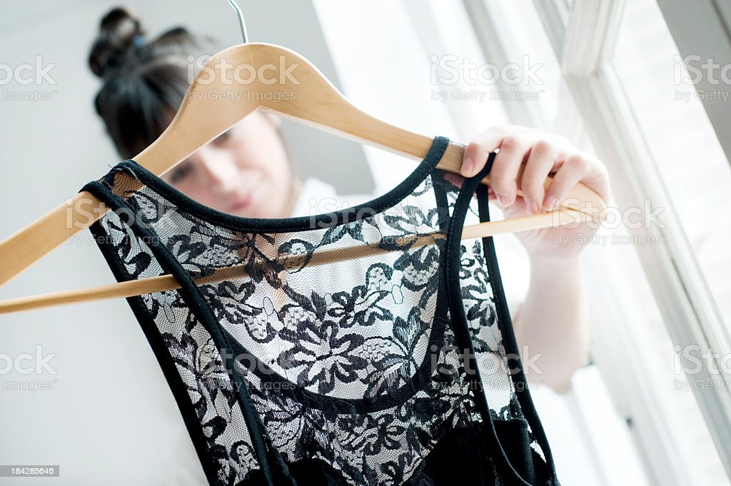 Young female adult looking at a laced black silk shirt stock photo