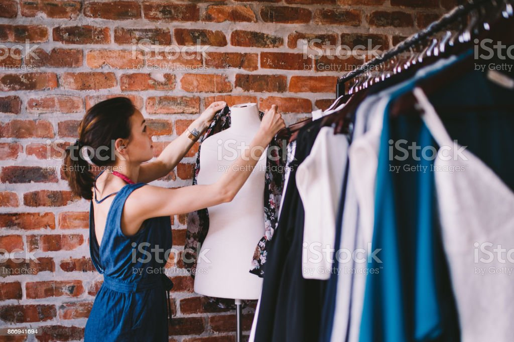 Young female adult working in fashion boutique stock photo
