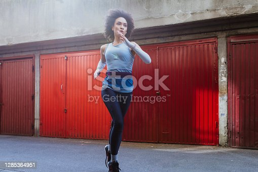 Fit health conscious woman with an Afro haircut doing morning exercises in the city