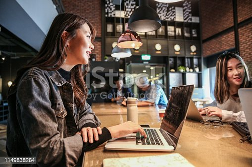 istock Young female and coworker discuss in front of computer 1149838264