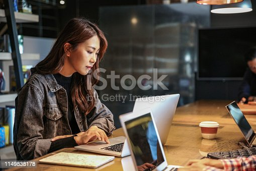 istock Young female and coworker working with computer 1149838178