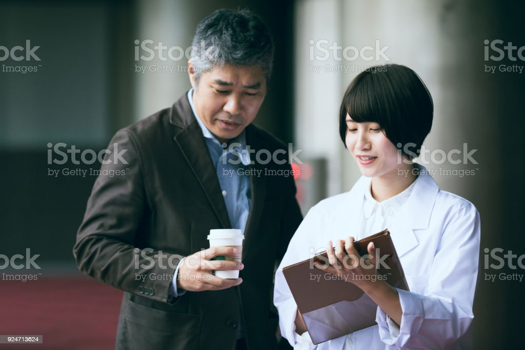 Young female and Middle age male engineer are conversing outside of office space. stock photo
