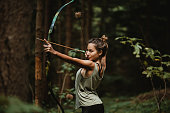 Young female archer practicing in the woods. Female hunter hunting in the forest by herself during the.