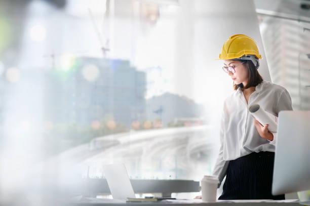 joven arquitecta de pie con su equipo en su oficina. concepto de trabajo de chica de construcción. - arquitecta fotografías e imágenes de stock