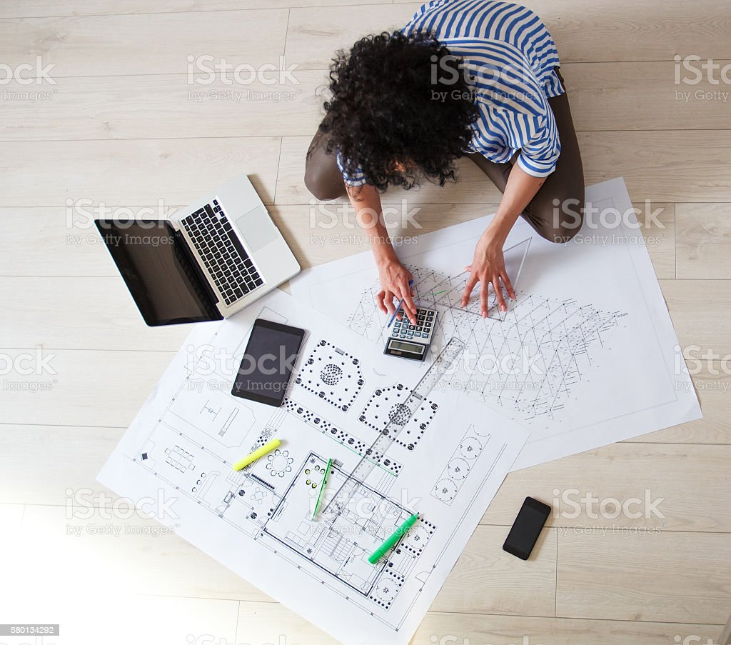 Young female architect working at home on the floor.