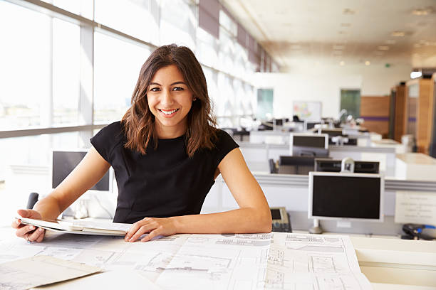 young female architect working with computer and blueprints - professional sport stock photos and pictures