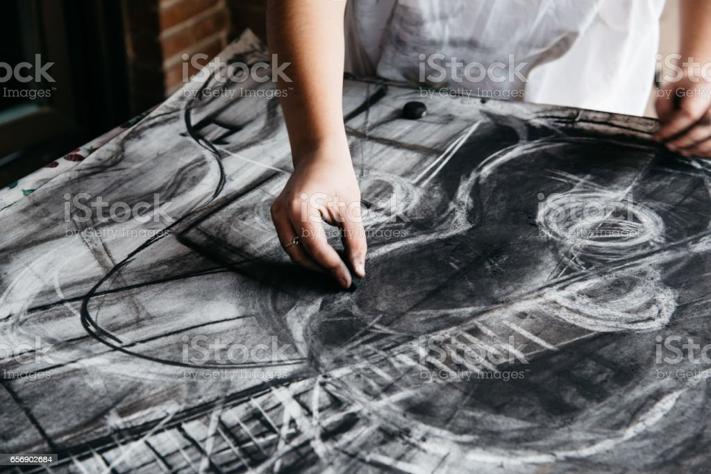 Young female artist painting with charcoal on paper stock photo