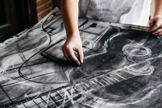 young female artist painting with charcoal on paper - charcoal drawing stock photos and pictures