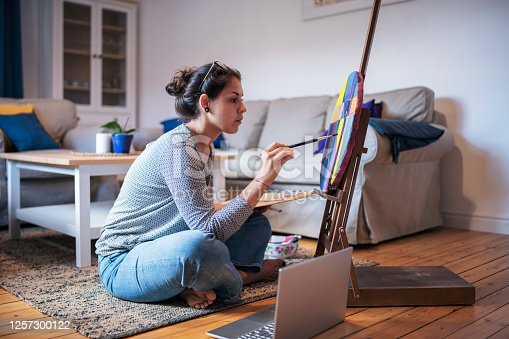 You female artist painting at home and using laptop.