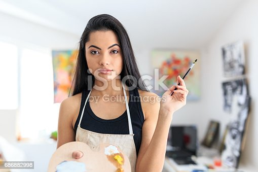 469937444 istock photo Young female artist posing in atelier 686882998
