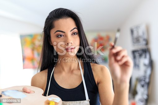 istock Young female artist posing in atelier 689569976
