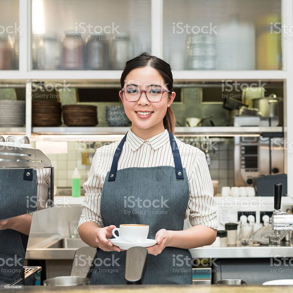 Young female Asian barista holding coffee at cafe counter stock photo