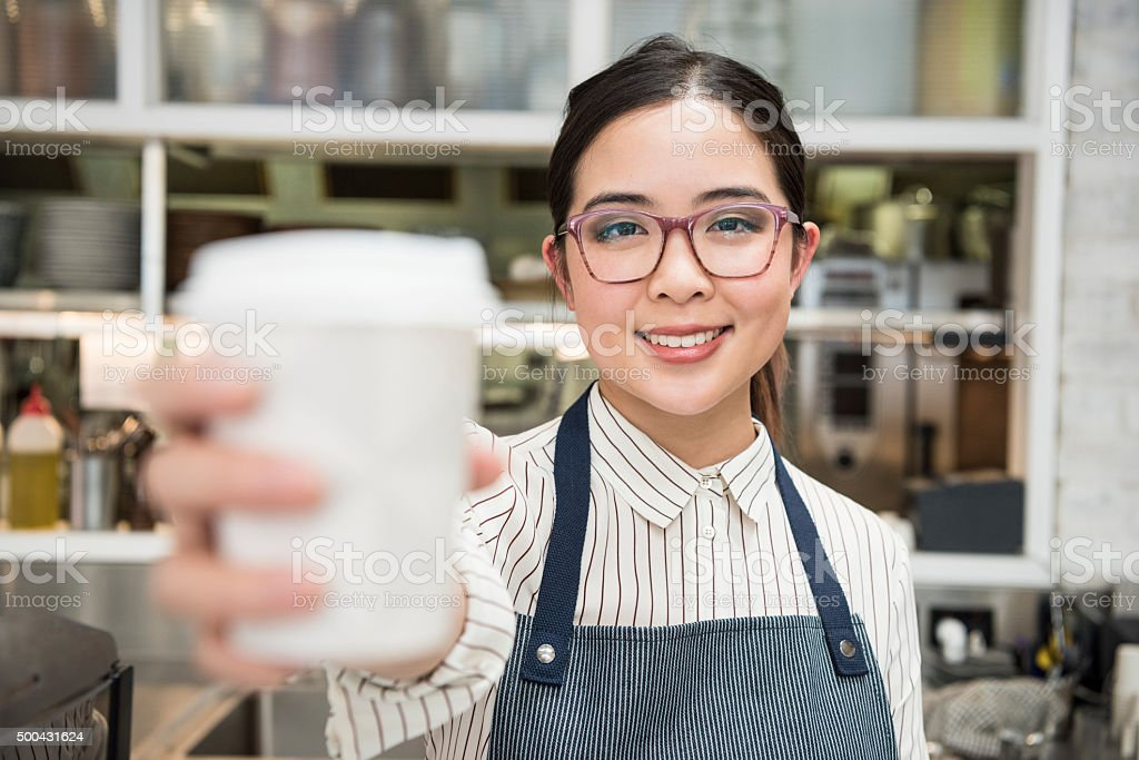 Young female Asian barista holding disposable cup towards camera stock photo