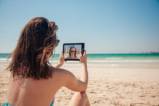 Young Female At The Seashore Taking Selfie stock photo