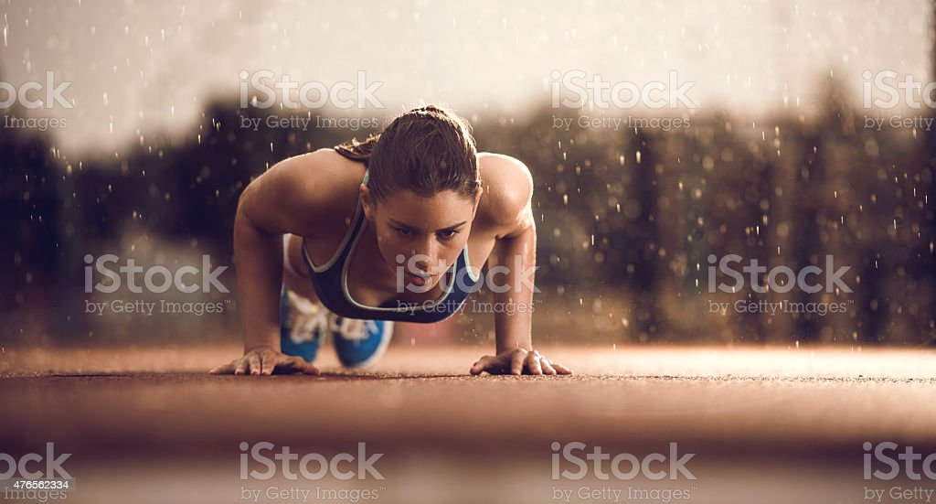 Young female athlete doing push-ups on a rain. stock photo