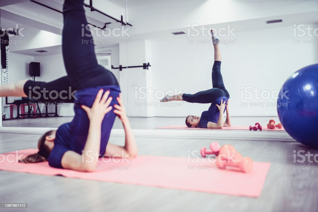 Young Female Athlete Doing the Lying on Back Bicycle Exercise in Gym stock photo
