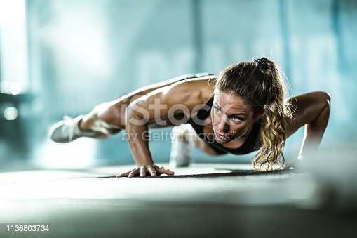 Athletic woman exercising push-ups in a health club. Copy space.